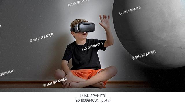 Young boy sitting cross legged, wearing virtual reality headset, reaching out to touch planet, digital composite