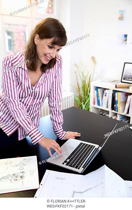 Happy woman using laptop in office
