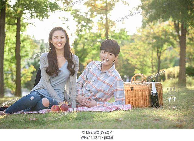 Young smiling couple having a picnic at park