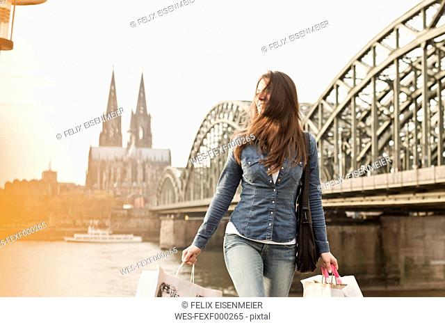 Germany, Cologne, young woman with shopping bags in front of Hohenzollern Bridge