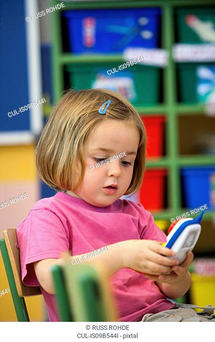 Preschool girl pressing toy cellphone buttons in classroom