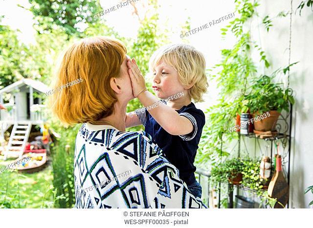 Litlte boy on his mother's arms on the balcony