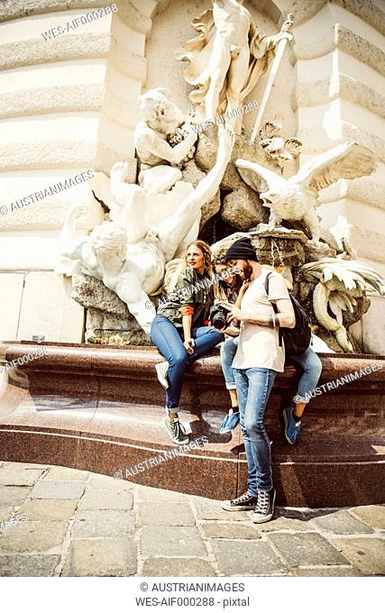 Austria, Vienna, group of three friends with camera in front of fountain at Hofburg Palace