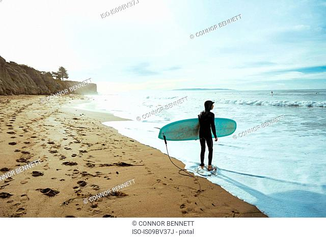 Surfer with surfboard on beach, Morro Bay, California, United States
