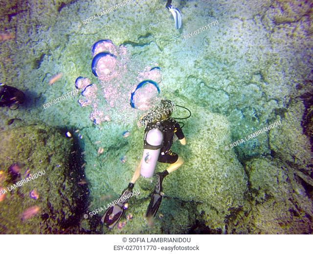 A scuba diver's bubbles from the top. View of the scuba diver gear, fins, tank, swimming underwater in the deep blue clear sea of Protaras, Cyprus