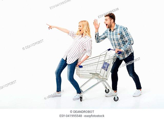 Full length portrait of an excited couple standing with a shopping trolley and pointing away isolated over white background