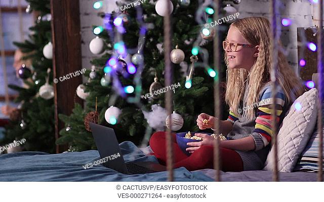 Cute teen girl watching funny cartoons on laptop
