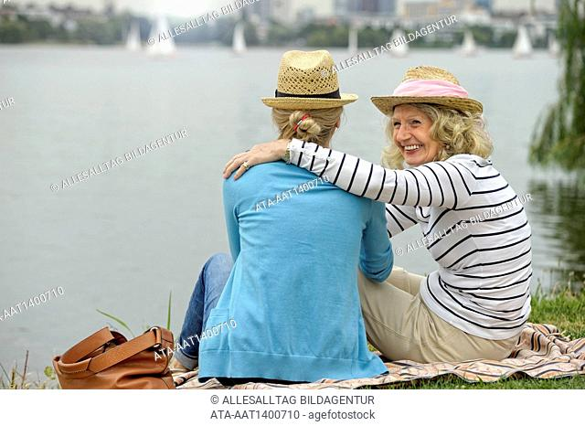 Mother and daughter sitting at the riverside