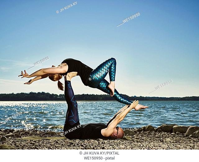 Sporty couple training aero yoga outdoors, summertime, sea and blue sky