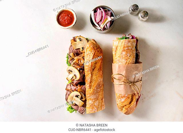 Opened and tied beef baguette sandwich with champignon mushrooms, green salad, fried onion with ingredients in row over white marble background