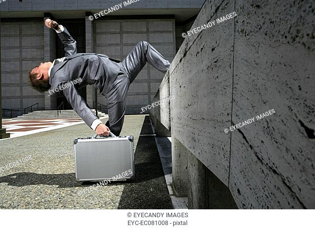 Businessman with briefcase bending backwards up a wall