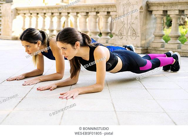 Two sportive young women exercising outdoors