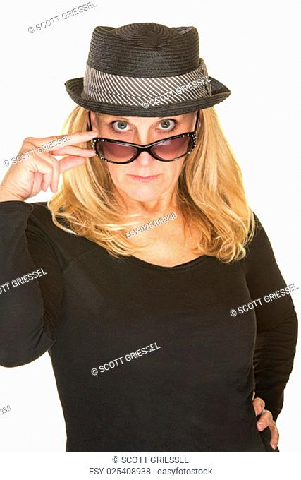 Cute woman in black with hat looking over sunglasses