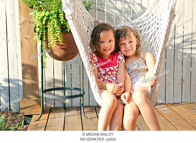 Girls sitting in hammock on porch
