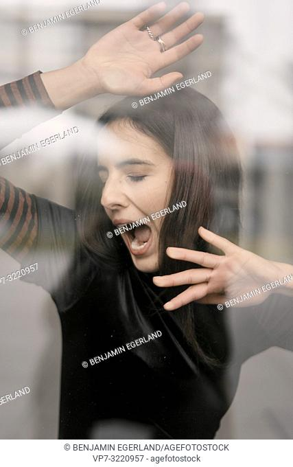 portrait of tired woman yawning behind glass window, in Munich, Germany