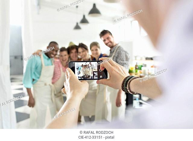Man photographing cooking class students in kitchen