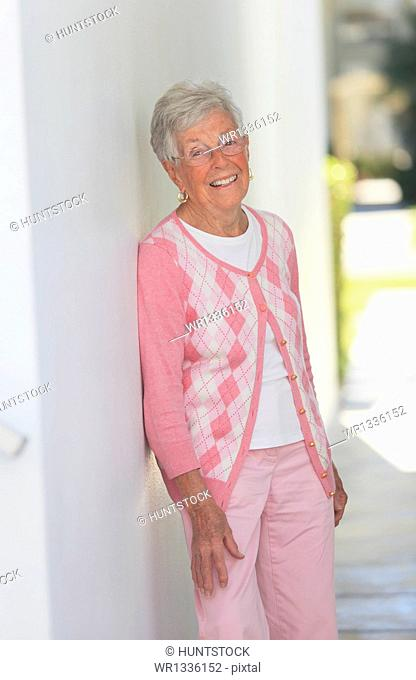 Senior woman smiling leaning against a wall