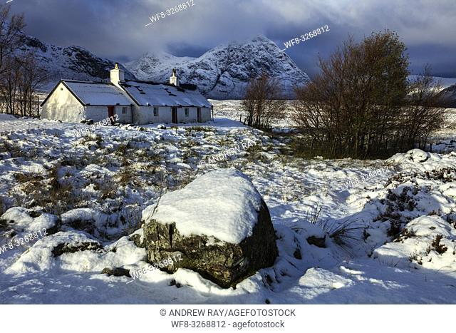 Black Rock Cottage on Rannoch Moor in the Scottish Highlands illuminated by the first rays of sunlight following an overnight snowfall in early November