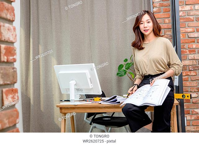 Young smiling businesswoman posing at office