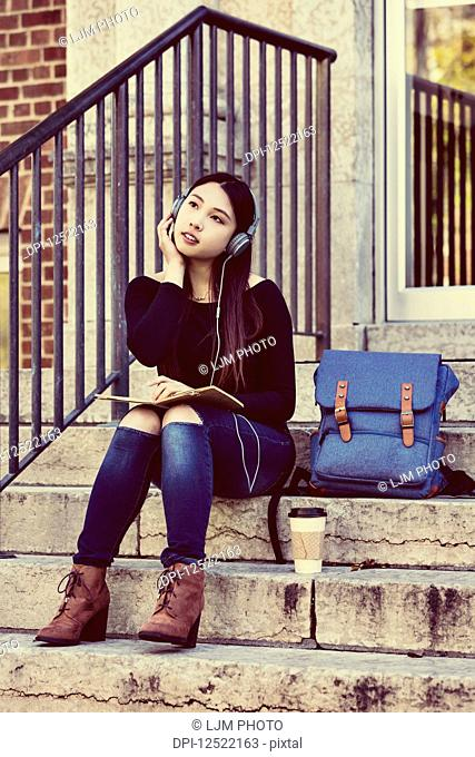 A young Chinese female university student sits on the steps listening to music using headphones and looks away while daydreaming; Edmonton, Alberta, Canada
