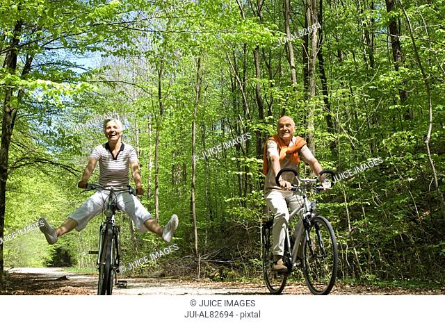 Senior couple riding bicycles on wooded road