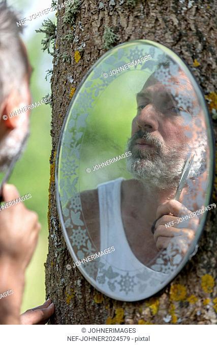 Mature man trimming beard