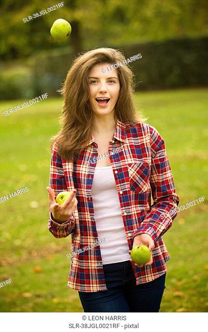 Teenage girl juggling apples in park