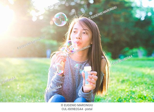 Young woman sitting in park blowing bubbles