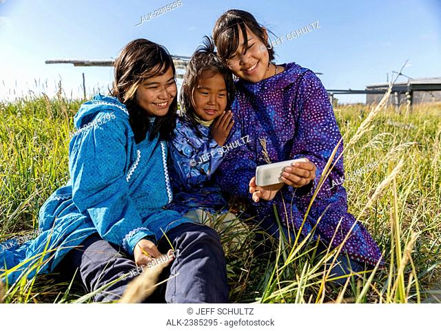 Athabascan girls in traditional kuspuks sitting in grass texting on smart phone with fish drying rack in background smiling, Nome, Alaska
