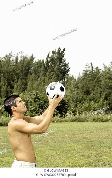 Side profile of a mid adult man holding a soccer ball