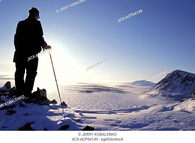 Hiker overlooking the snowy northwest coast of Ellesmere Island, Nunavut, Canada