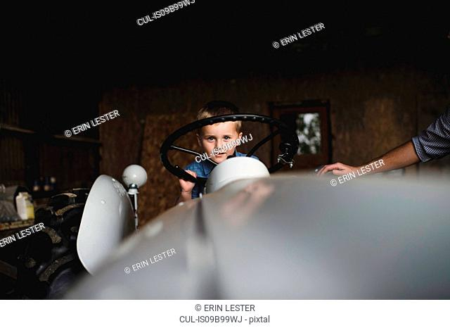 Boy on tractor holding steering wheel looking at camera