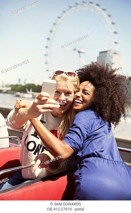 Enthusiastic friends taking selfie on double-decker bus with London Eye in background