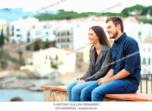 Happy couple or friends looking away on vacation sitting on a ledge in a coast town