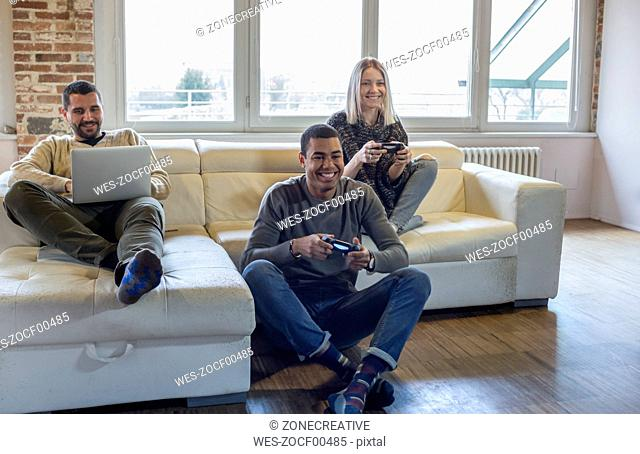 Friends playing computer game at home