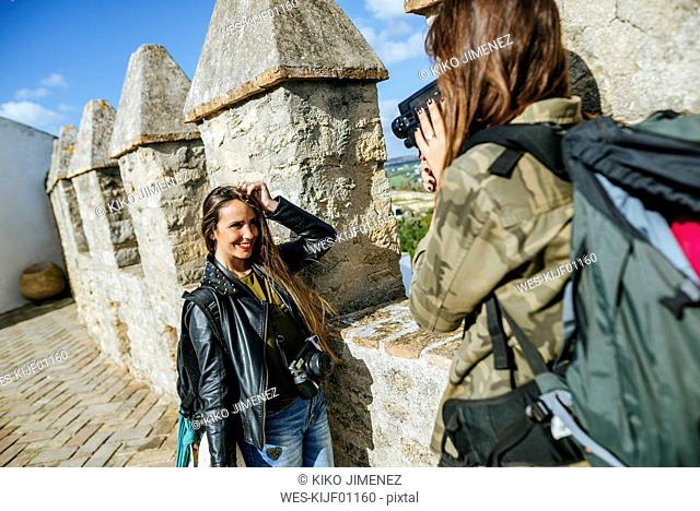 Young traveling women recording with old video camera