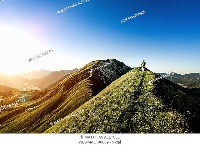 Germany, Allgaeu Alps, woman running on mountain ridge