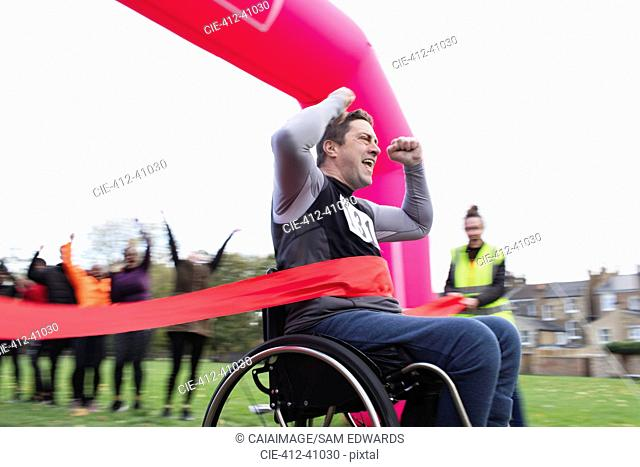 Enthusiastic man in wheelchair crossing finish line, cheering at charity race in park