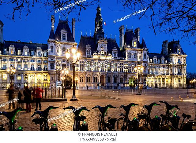 France, Paris, Hotel de ville (city hall) at night, shared bikes in the foreground