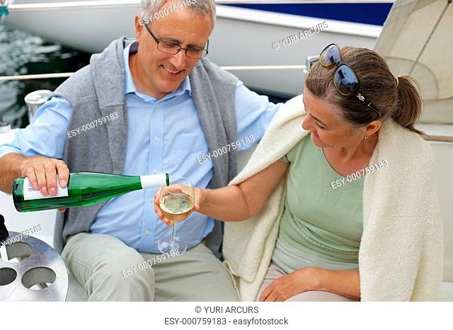 Mature man refilling wife's champagne glass while on a sailboat