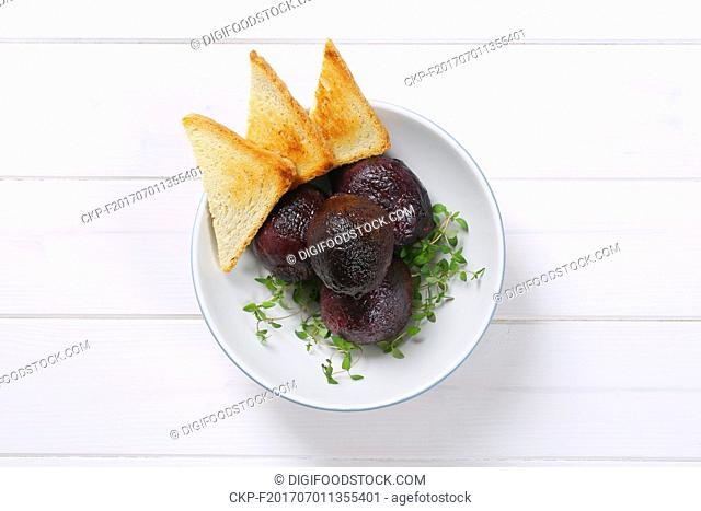 bowl of baked whole beet with toast on white wooden background