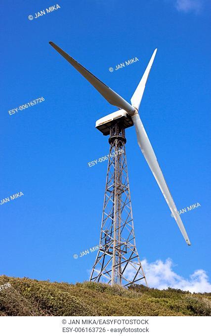 Wind turbine on the green hill with blue sky Tarifa, Cadiz, Andalusia, Spain