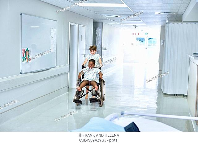 Boy patients pushing female friend in wheelchair on hospital children's ward