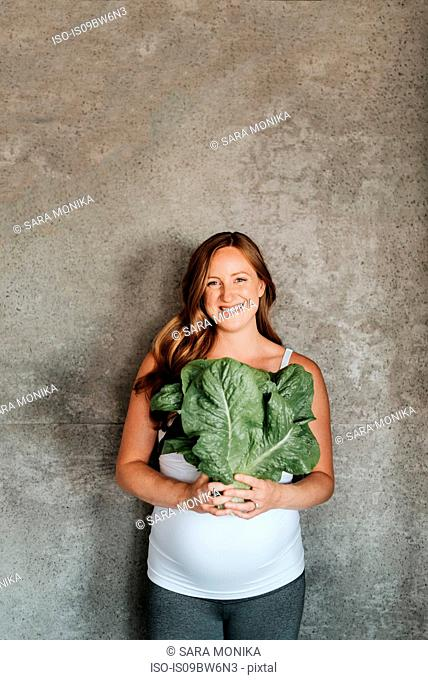 Pregnant woman holding up lettuce