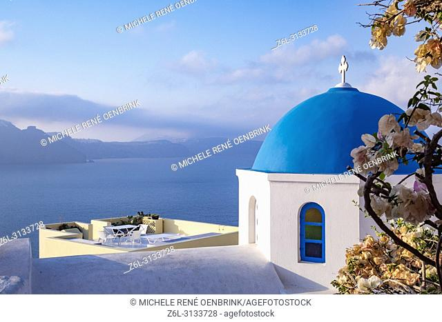 Blue domed Greek Orthodox church with bougainvillea flowers in Oia, Santorini Greece