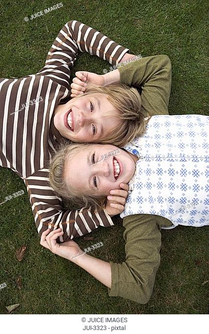 Boy and girl 8-11 lying cheek to cheek on grass, smiling, portrait, front view, overhead view