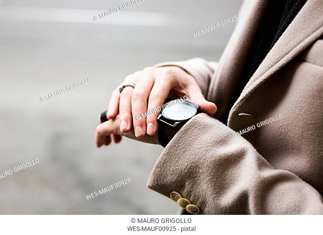Close-up of man outdoors checking the time
