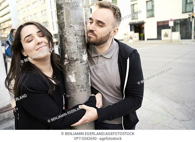blithe couple embracing street lamp post at street in city, insouciance, frivolous