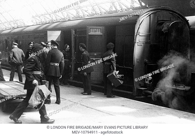 NFS personnel helping to load luggage from a trolley onto a train at St Pancras railway station, 14 July 1944, as part of an evacuation exercise during a period...