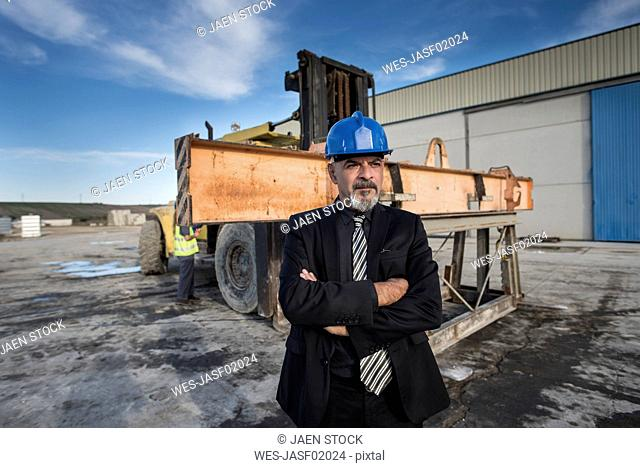 Confident businessman standing on industrial site near bulldozer with femaleworker in background